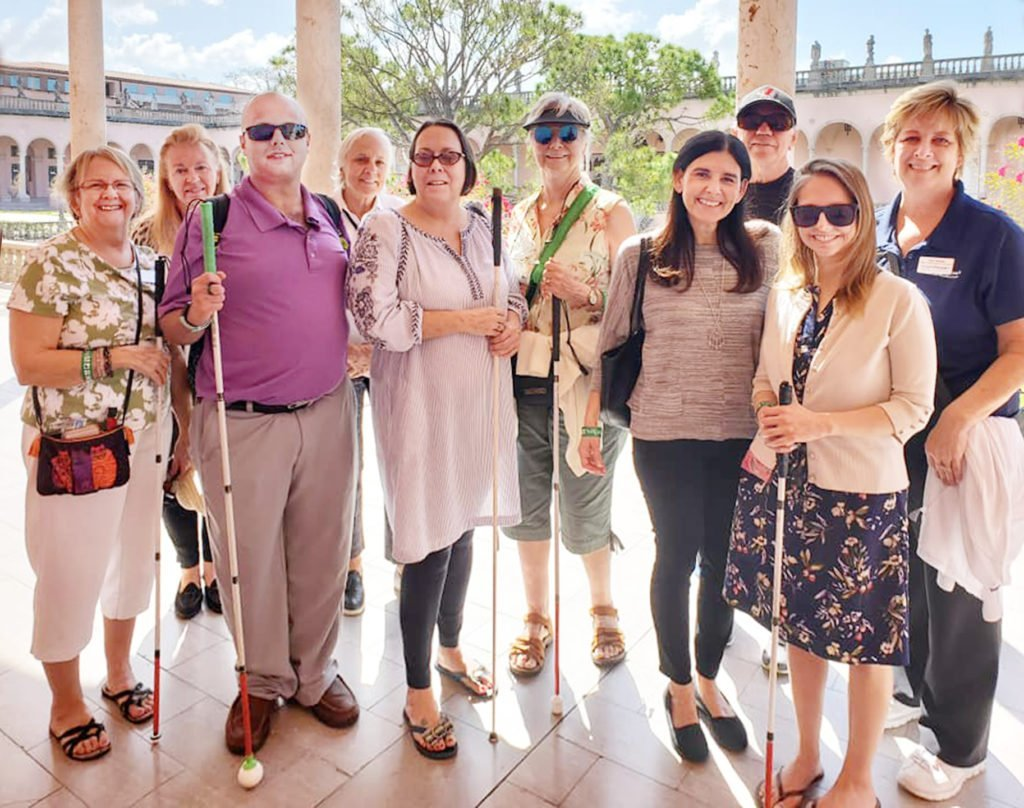 A group of Lighthouse staff, instructors and clients outside in the courtyard at The Ringling Museum.