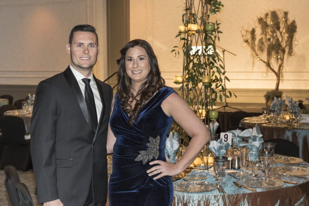 a man wearing a suit and tie standing with a woman wearing a navy blue velvet gown at the 2020 art in the dark event