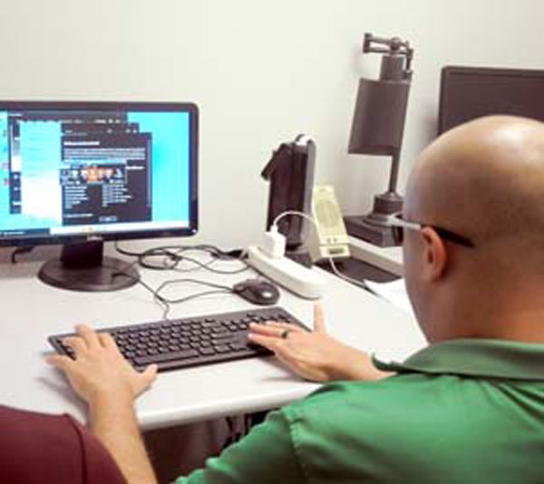 man wearing green shirt using computer