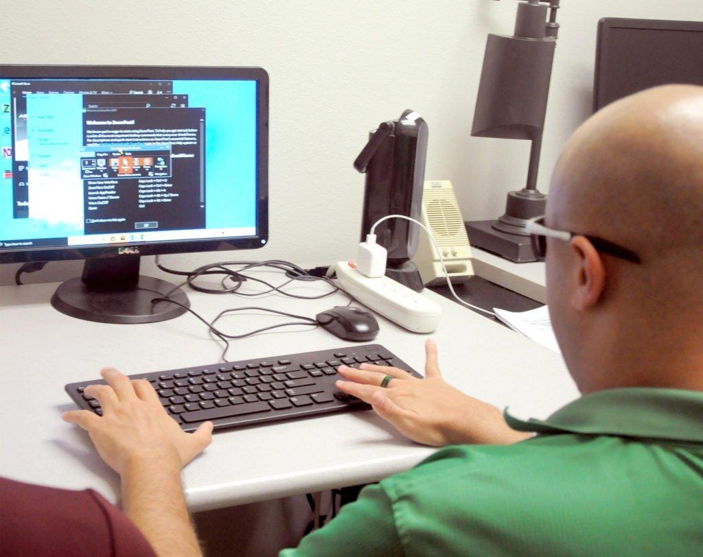 Man using keyboard and monitor