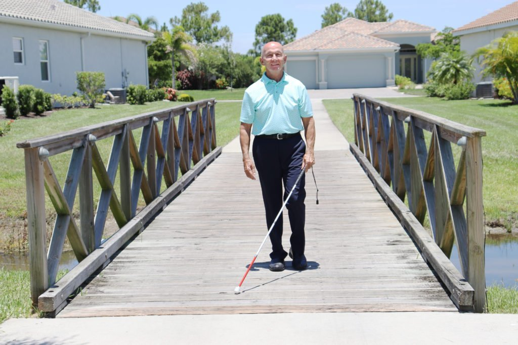 An older gentleman with a light blue shirt and dark pants crossing a wooden bridge with his white cane.