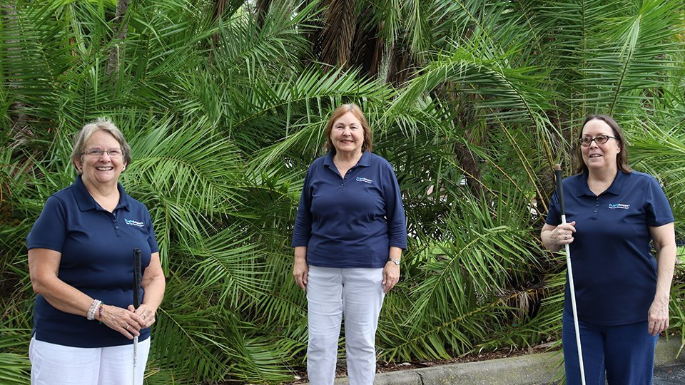 three female staff members wearing navy blue lighthouse shirts standing outside in from of palm trees