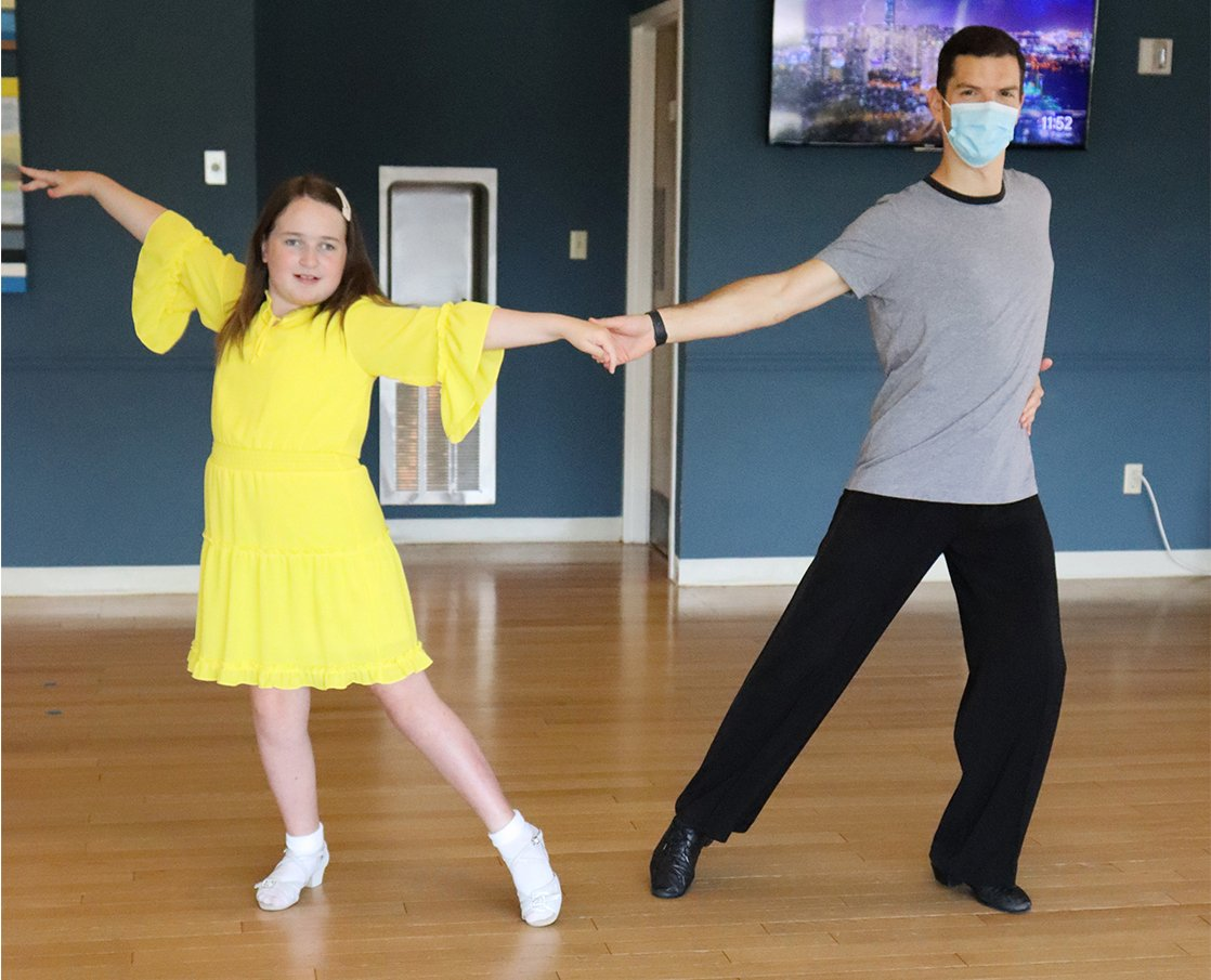 young girl wearing a yellow dress and white shoes dancing with male instructor wearing a face mask