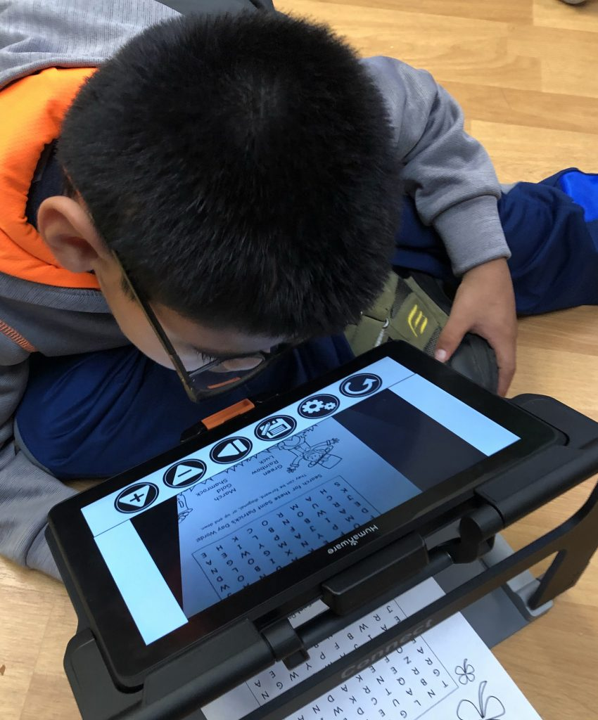 A boy uses an electronic magnifier to view a puzzle