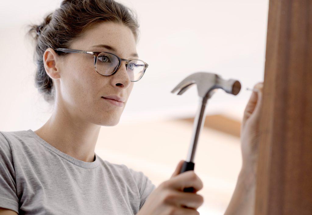 woman repairing a door at home