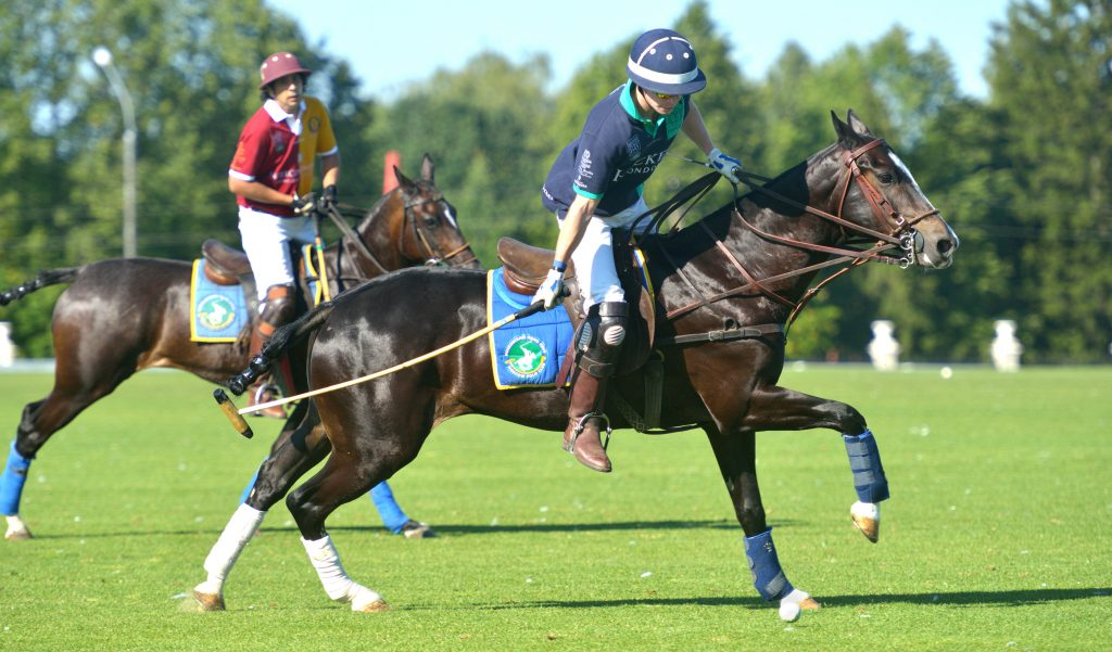 Two riders close in on the ball during a polo match.