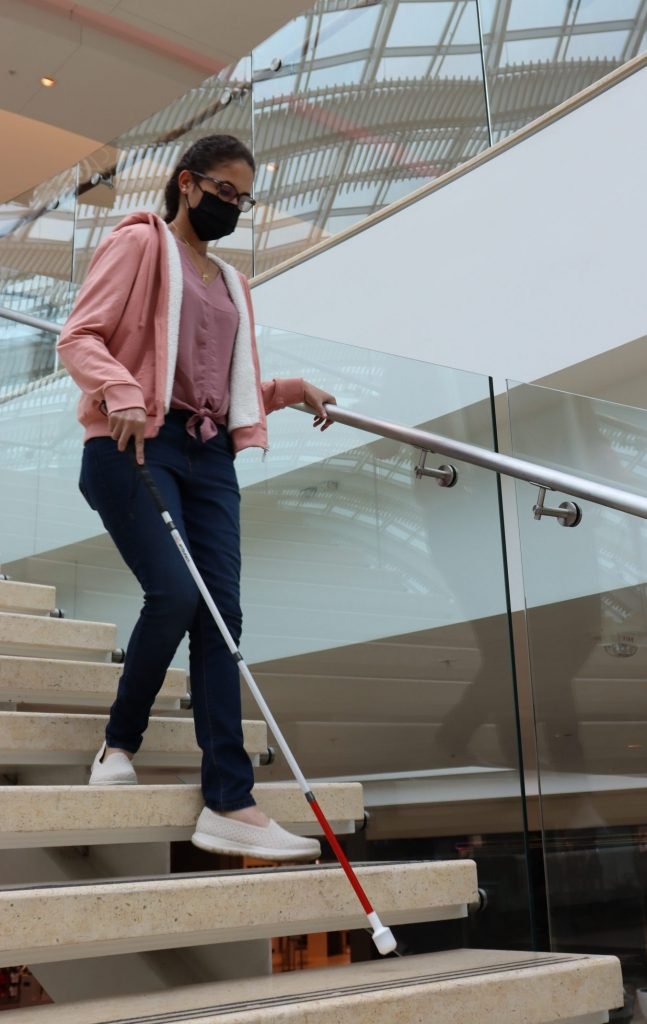 Brianna walking down stairs with white cane
