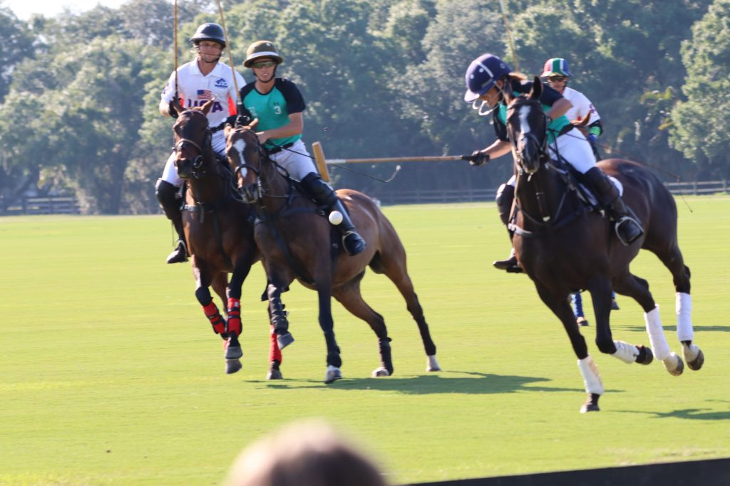 Polo player hitting ball on horse with three others