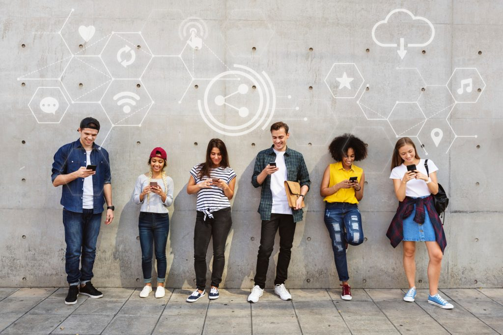 Six students standing in front of a wall on their mobile phones