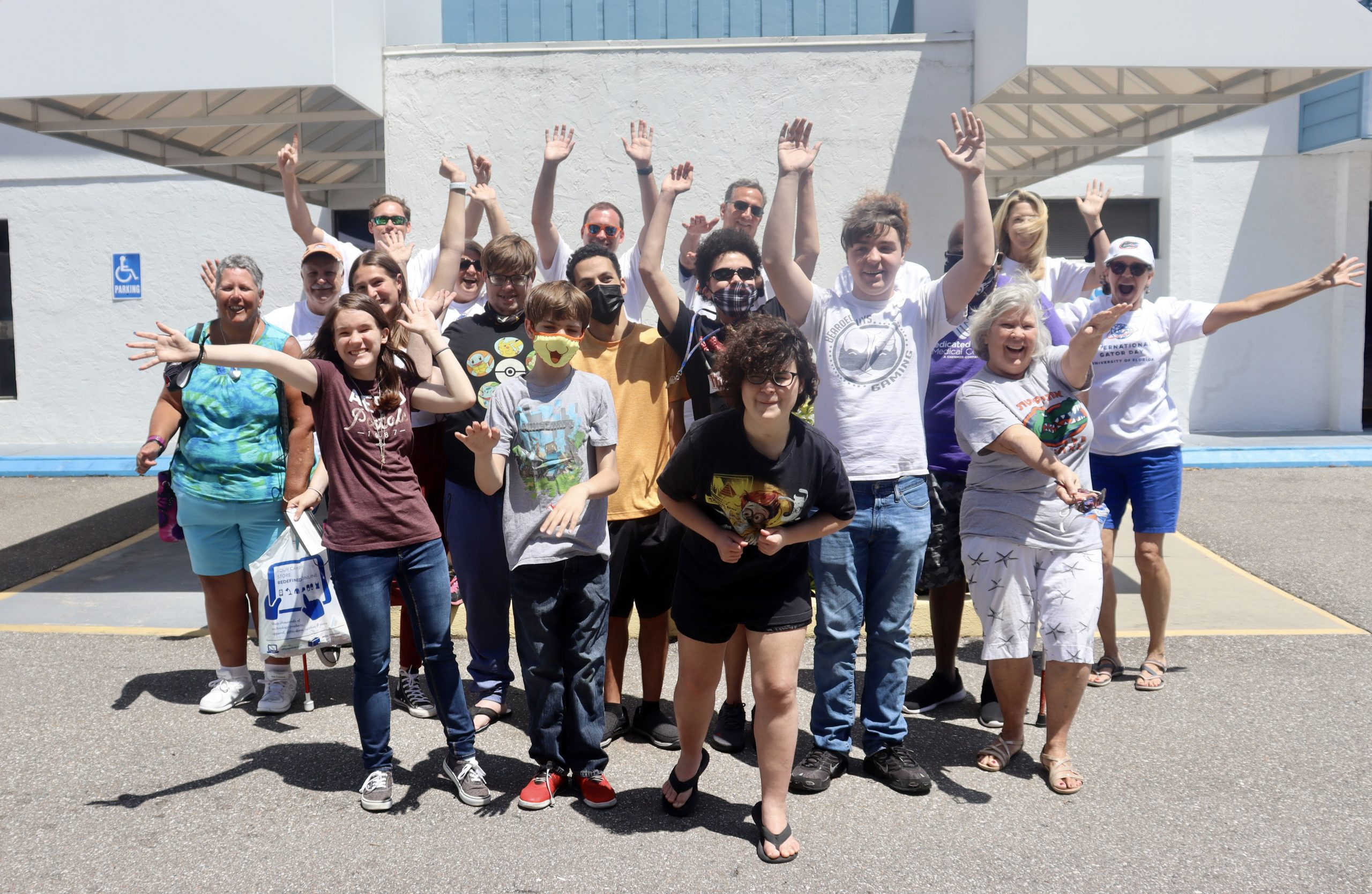 A large group of teens and adults with their hands up in front of the Lighthouse building on a sunny day.